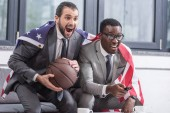 happy multicultural business partners with american flag watching basketball match in office