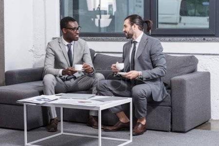 multiethnic businessmen sitting on couch, looking at each other and drinking coffee in office