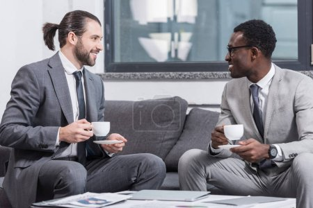 successful multiethnic businessmen sitting on couch and drinking coffee in office