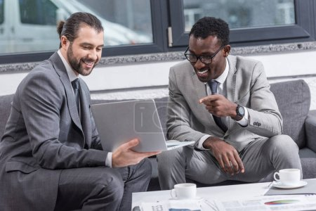 african american businessman sitting on couch and pointing with finger at business partners laptop in office