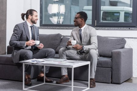 Photo for Multiethnic businessmen sitting on couch and drinking coffee in office - Royalty Free Image