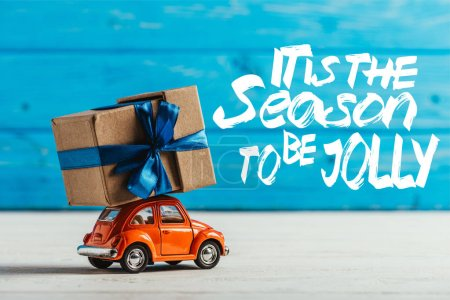 """close-up shot of toy car with gift box on blue wooden background with """"it is the season to be jolly"""" inspiration"""