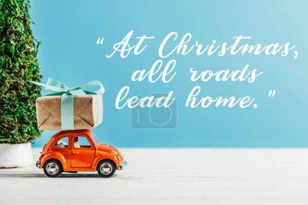 Photo pour Gros plan de véhicule-jouet avec boîte-cadeau sur fond bleu avec «à Noël tous les chemins mènent Accueil» inspiration - image libre de droit
