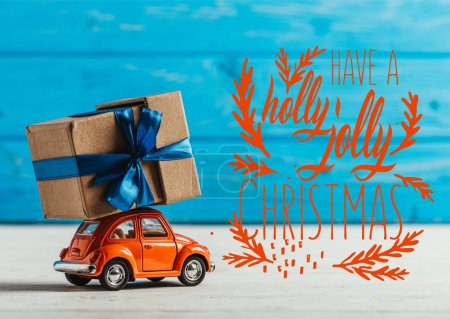"""close-up shot of toy car with gift box on blue wooden background with """"have a holly jolly christmas"""" inspiration"""