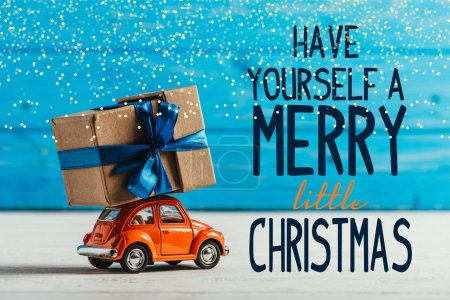 """close-up shot of toy car with gift box on blue wooden background with """"have yourself a merry little christmas"""" inspiration"""