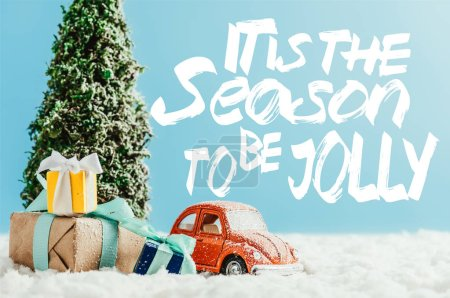 """close-up shot of toy red car with presents and christmas tree standing on snow made of cotton on blue background with """"it is the season to be jolly"""" inspiration"""