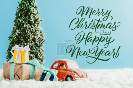 """close-up shot of toy red car with presents and christmas tree standing on snow made of cotton on blue background with """"merry christmas and happy new year"""" lettering"""