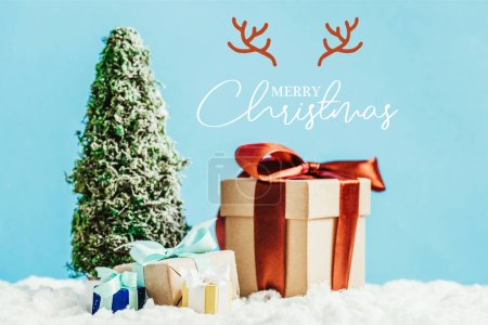 """close-up shot of christmas gifts and miniature christmas tree standing on snow on blue background with """"merry christmas"""" lettering with deer horns"""