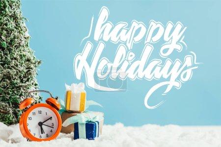 """Photo pour Gros plan des cadeaux de Noël avec réveil et sapin de Noël miniature debout sur la neige sur fond bleu avec lettrage """"Joyeuses fêtes"""" - image libre de droit"""