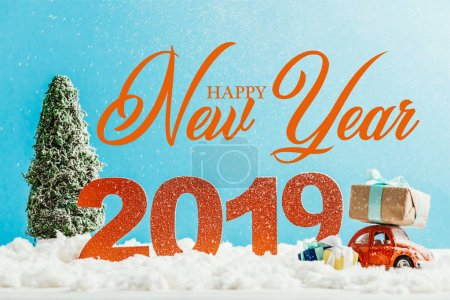 """big red 2019 numbers with toy car, gifts and christmas tree on snow with """"happy new year"""" lettering"""