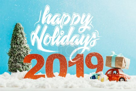 """Photo for Big red 2019 numbers with toy car, gifts and christmas tree on snow with """"happy holidays"""" lettering - Royalty Free Image"""