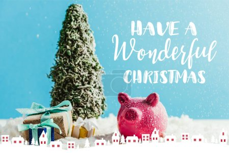 """miniature christmas tree with gifts and piggy bank standing on snow on blue background with """"have a wonderful christmas"""" inspiration with houses illustration"""