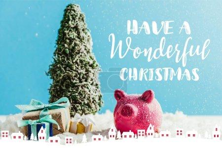 """Foto de Árbol de Navidad en miniatura con regalos y alcancía sobre nieve en fondo azul inspiración """"tener una Navidad maravillosa"""" con casas de ilustración - Imagen libre de derechos"""
