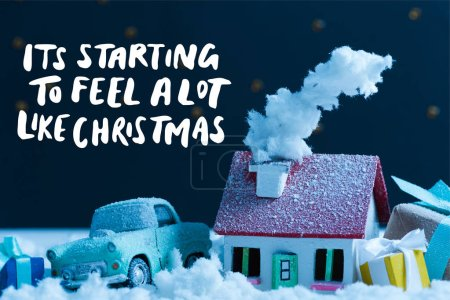 """Photo for Close-up shot of miniature car with christmas gifts and house covered with snow at night, with """"it is starting to feel a lot like christmas"""" inspiration - Royalty Free Image"""