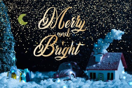 """Photo pour Gros plan de voiture jouet avec cadeaux de Noël et maison couverte de neige la nuit, avec lettrage """"joyeux et lumineux"""" - image libre de droit"""