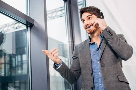 handsome call center operator standing by window, touching headset and speaking in microphone in office