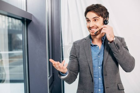 smiling call center operator standing by window and speaking in microphone in office