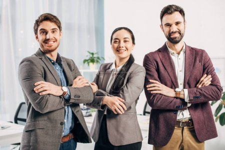 smiling office managers with arms crossed looking at camera in office