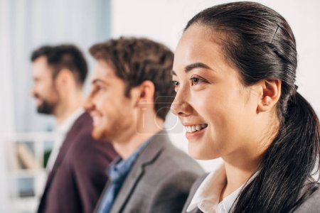 close up view of pretty office manager with colleagues on background
