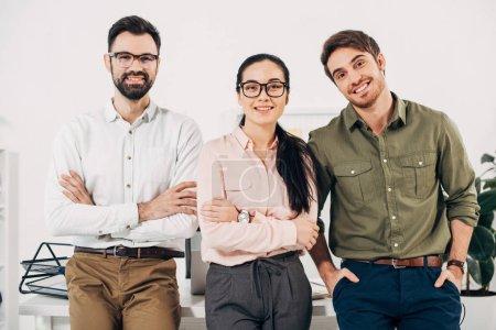 Photo pour Gestionnaires de bureau les bras croisés en souriant et en regardant la caméra dans le bureau - image libre de droit