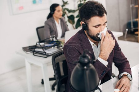 sick call center operator with napkin blowing nose with coworker on background