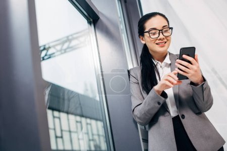 smiling businesswoman standing by window and touching smartphone screen