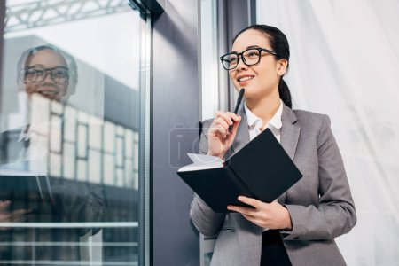 pretty businesswoman smiling, standing by window and holding notebook and pen