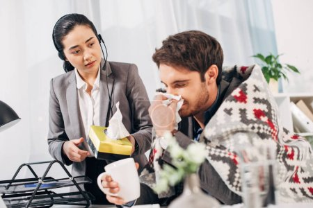 disquieted call center operator giving napkins to sick coworker with blanket and cup in office