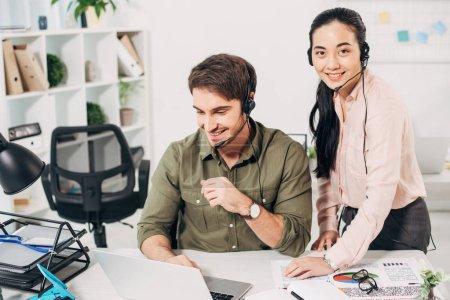 Photo pour Souriant opérateur de centre d'appel au portable et jolie collègue en regardant la caméra dans le bureau - image libre de droit