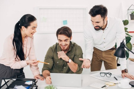 smiling managers sitting at desk and pointing at laptop screen in office