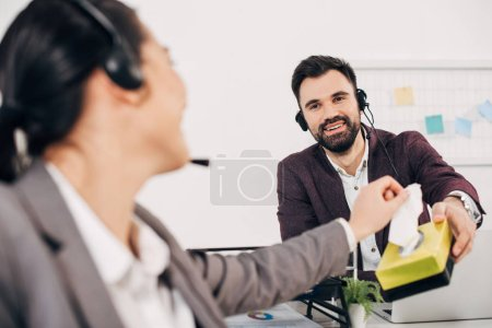 smiling call center operator giving napkins to coworker in office
