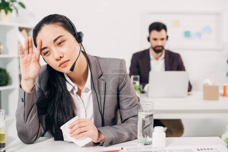 sick call center operator touching head and holding napkin in office