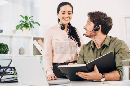 handsome call center operator holding notebook and looking to pretty colleague in office