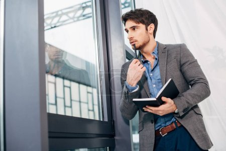 thoughtful businessman standing by window and holding notebook in office