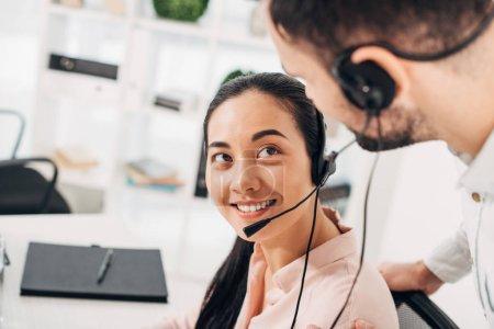 Photo pour Opérateur centre d'appel attrayant de souriant et regardant collègue au bureau - image libre de droit