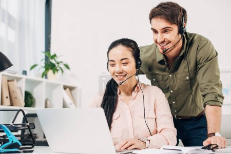 call center operators smiling and looking at laptop screen in office