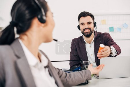 handsome call center operator smiling and giving bottle with medicine to coworker in office