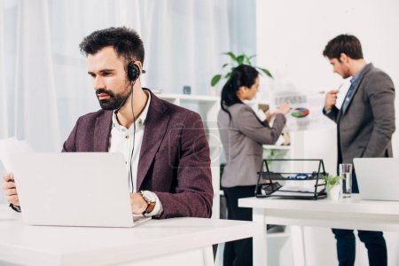 call center operator working at laptop with coworkers on background in office