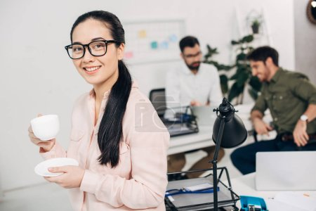 attractive office manager holding coffee cup and looking at camera with coworkers on background