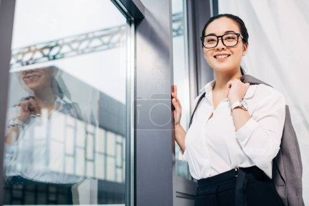smiling businesswoman with jacket over shoulder standing by window and looking at camera in office