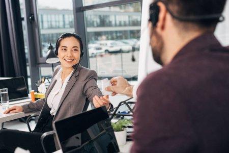 Photo pour Appelez le centre opérateur donnant bouteille avec médecine à souriant collègue au bureau - image libre de droit