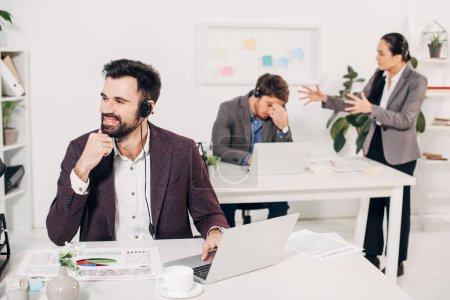 Photo pour Opérateur de centre d'appel assis au bureau avec des collègues bagarres sur fond de sourire - image libre de droit