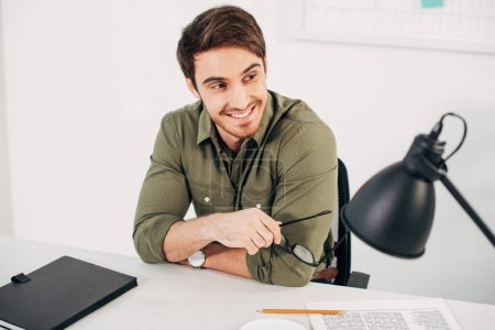 Photo for Handsome office manager sitting at desk, smiling and holding glasses - Royalty Free Image