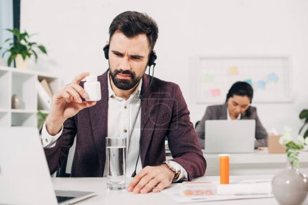 sick call center operator sitting at desk and holding pill bottle in office