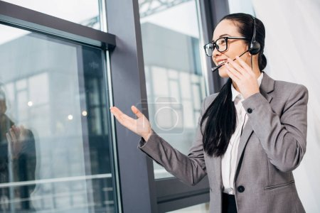 pretty call center operator touching headset and speaking in microphone by window in office