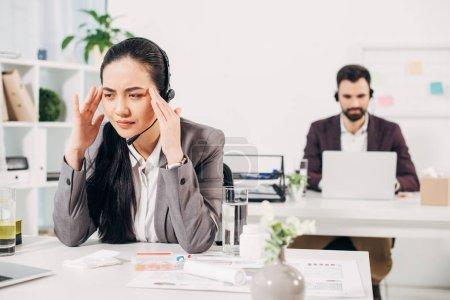 sick call center operator touching head in office