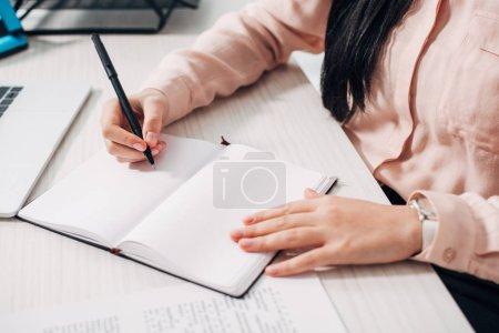 Photo pour Recadrée vue de femme tenant le stylo et écrire dans cahier - image libre de droit