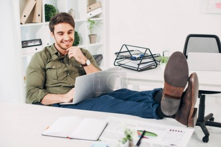 Cheerful businessman sitting on chair with legs on table and looking at laptop in office