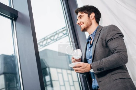 Young businessman holding cup of coffee and looking in window
