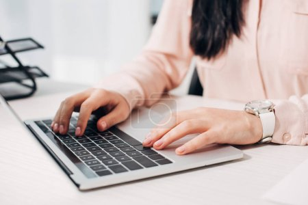 Cropped view of businesswoman typing on computer keyboard in office